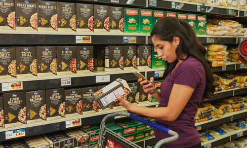 A woman scanning the grocery item with her phone